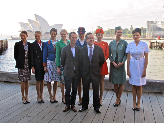 Martin Grant with Qantas CEO Alan Joyce with models wearing each of Qantas' uniforms since 1948
